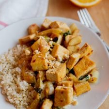 Orange tofu stir-fried with fennel and served over brown rice on the white plate.