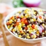 Black bean and corn salad with red onion, bell pepper and cilantro in a white bowl.
