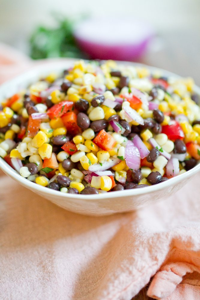 Black bean and corn salad with red onion and cilantro in a bowl.
