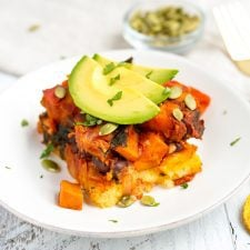 Mayan harvest bake on a white plate with layers of polenta and quinoa with roasted sweet potatoes, plantains. Topped with avocado.