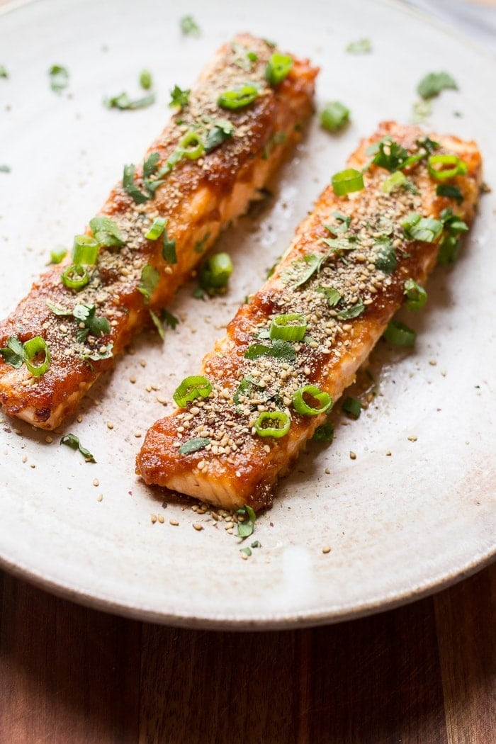 Two pieces of miso broiled salmon with sesame seeds and scallions on top.