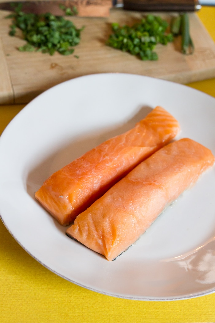 Two pieces of raw salmon on a white plate