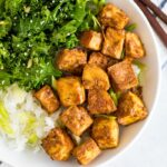 White bowl with kale topped with sesame seeds, crispy baked peanut tofu, and rice topped with scallions. Chop sticks are next to the bowl. The bowl is sitting on a blue and white striped folded napkin.