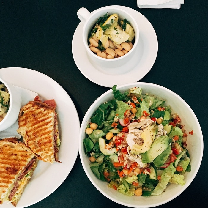 Meal from Union Market in Richmond, VA. Three plates, one with sandwich, one with green chopped salad and one with white bean salad
