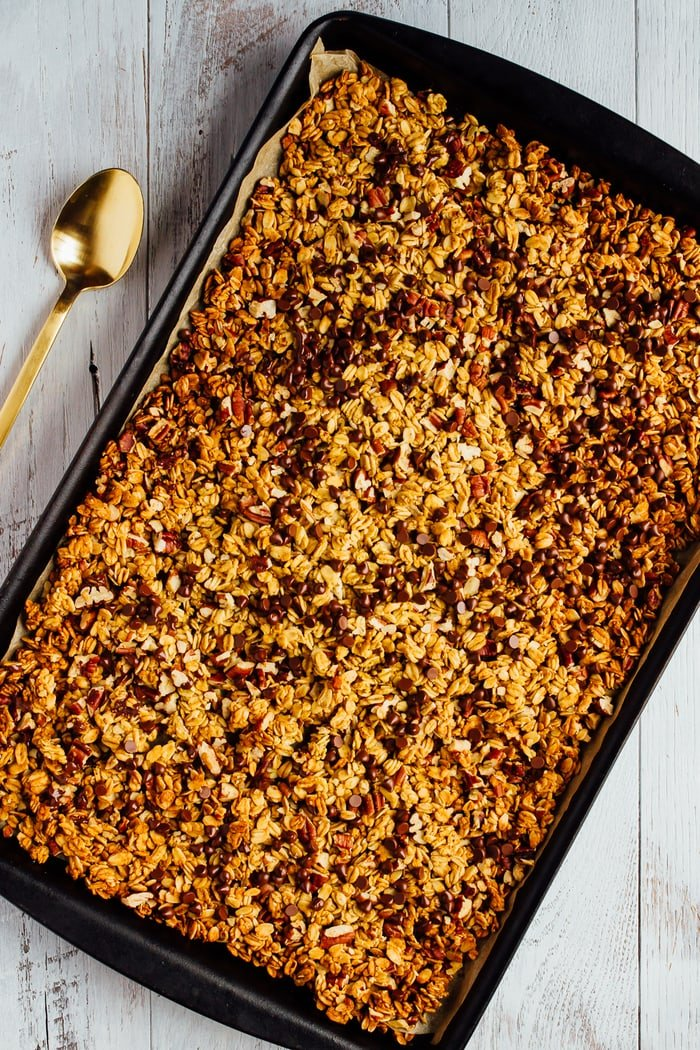 Chocolate Pecan Pumpkin Granola on a baking sheet with a spoon to the side.