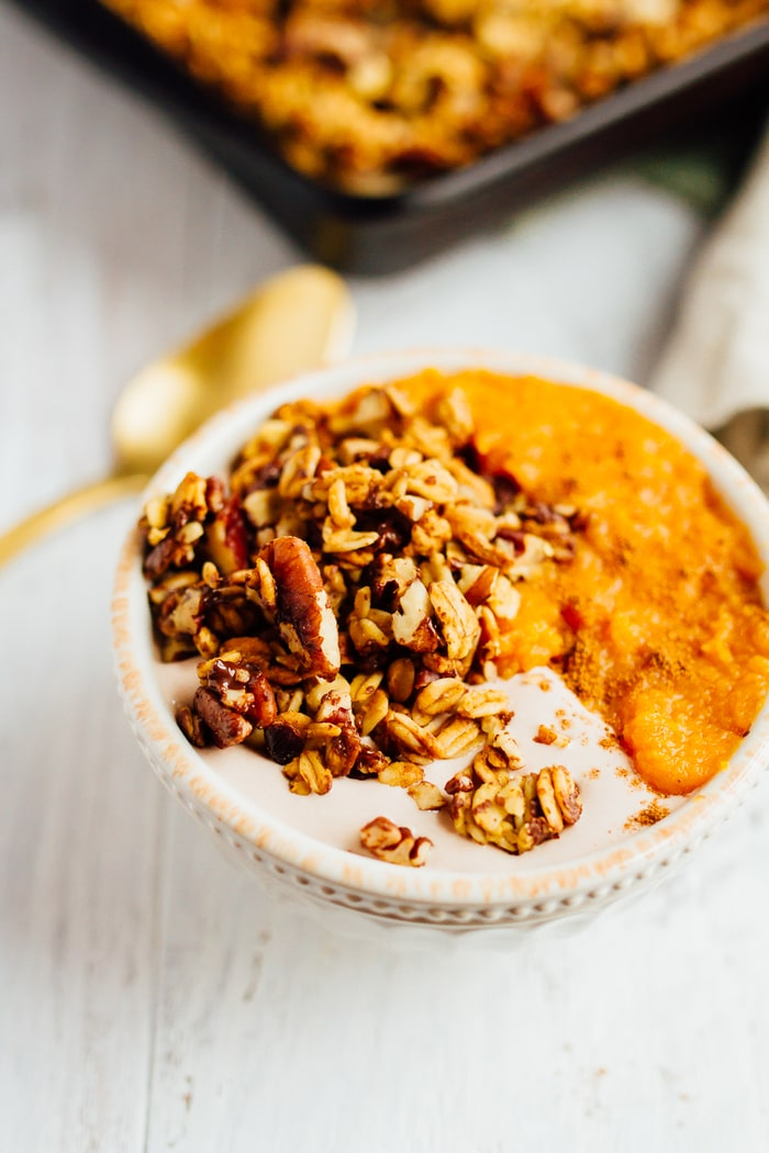 Pumpkin granola in a bowl with yogurt and pumpkin puree. A spoon and the baking tray is in the background.