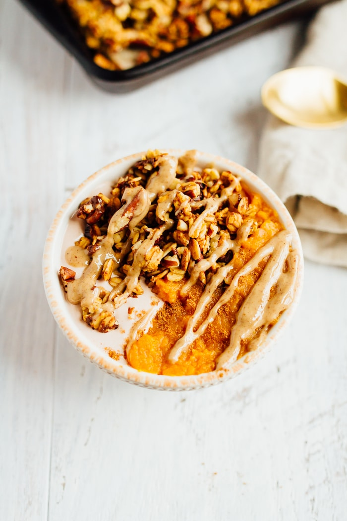 Chocolate Pecan Pumpkin Granola Bowl of yogurt, granola and pumpkin topped with a drizzle of nut butter.