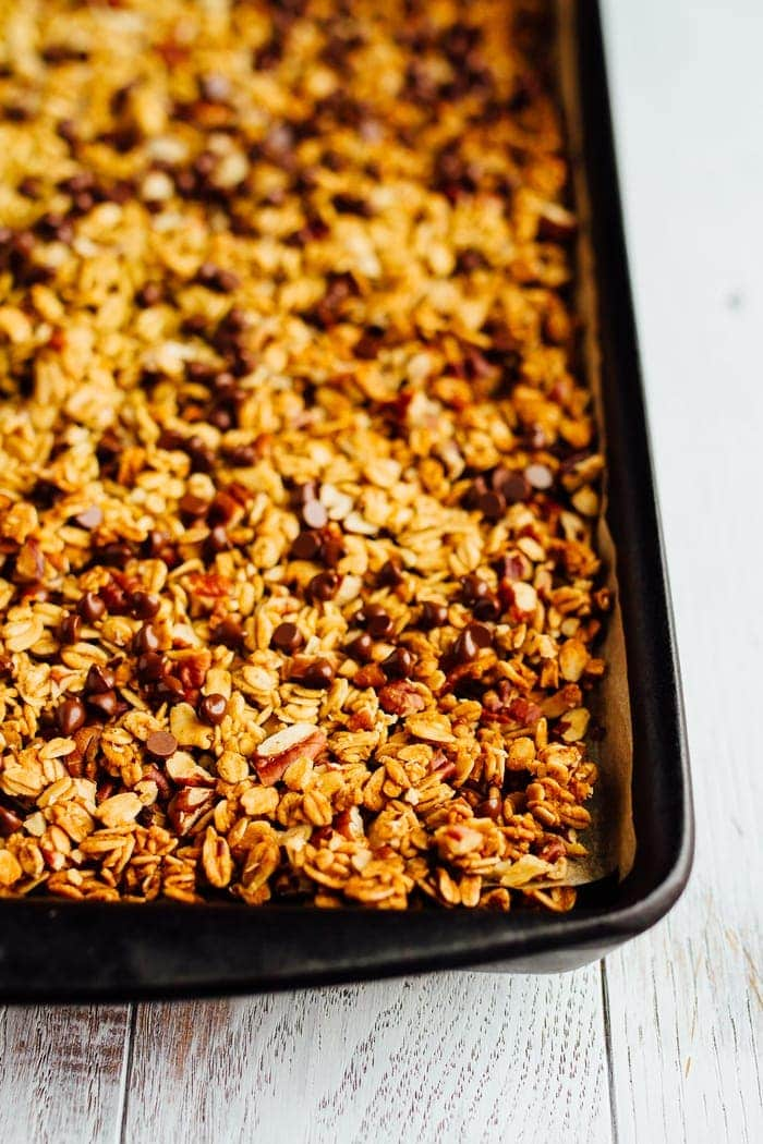 Close up image of pumpkin granola on a baking sheet lined with parchment paper.