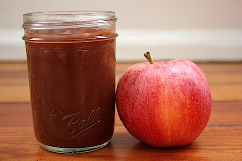 Healthy Homemade Apple Butter in clear mason jar on wood table next to whole apple.