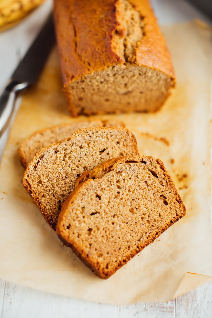 Whole wheat healthy banana bread loaf with three slices cut in front.