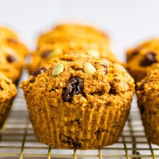 Pumpkin bran muffins stuffed with pumpkin seeds and raisins on a cooling rack.