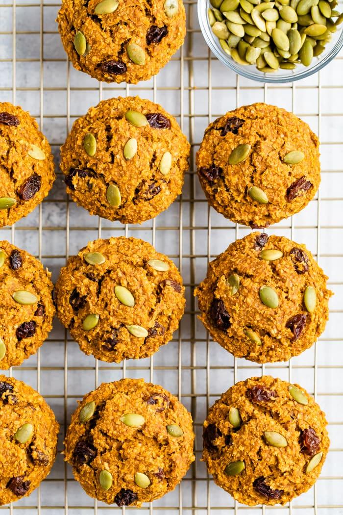 Pumpkin bran muffins on a cooling rack next to a bowl of pumpkin seeds.