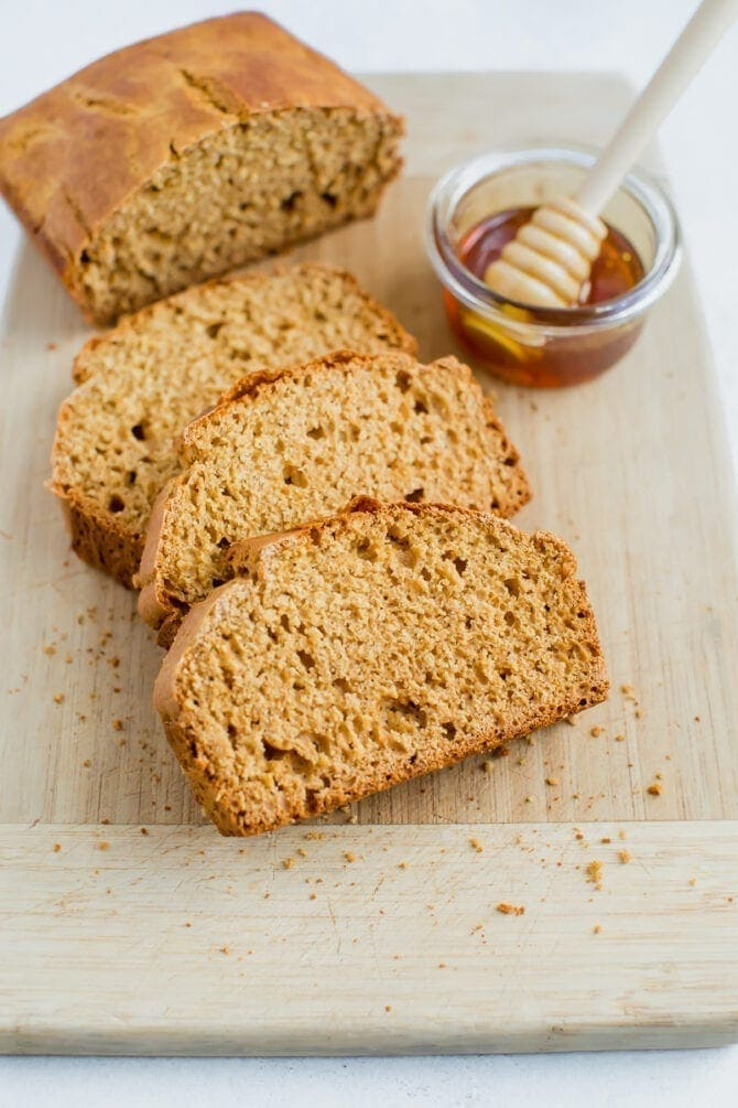 Three slices of honey whole wheat brown bread with the remaining loaf on a cutting board. There is a small dish of honey with a wooden honey comb resting inside the dish.