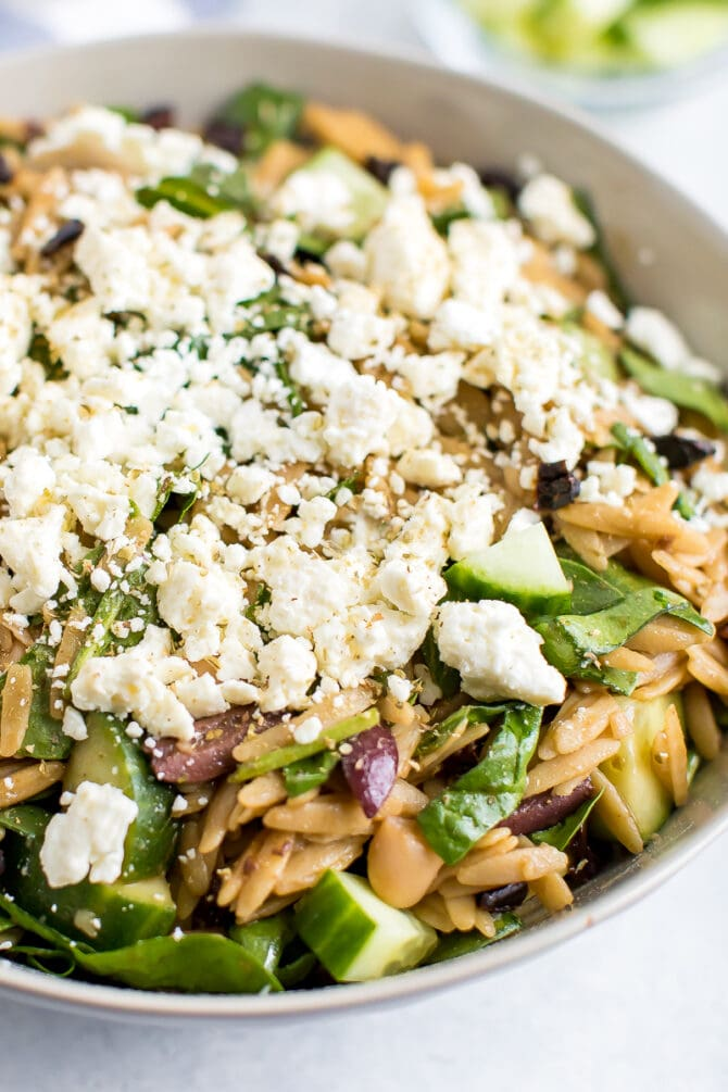 Orzo pasta salad in a bowl, topped with feta.