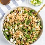 Orzo pasta salad tossed with a balsamic dressing. Orzo mixed with spinach, cucumber, feta, sun-dried tomatoes, olives and seasoning. Bowls of cucumber, feta and balsamic dressing in the background.