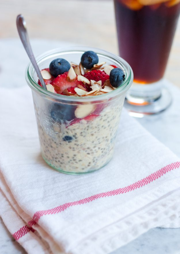 Clear jar with overnight oats, berries, and nuts sitting on a kitchen towel.