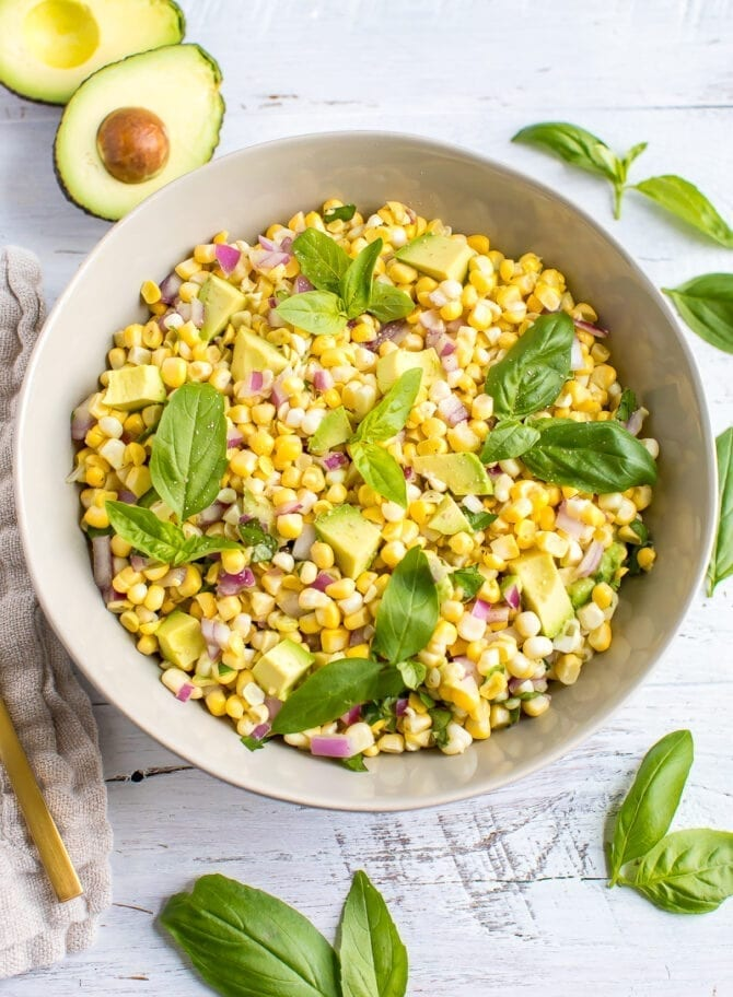 Avocado and corn salad topped with fresh basil