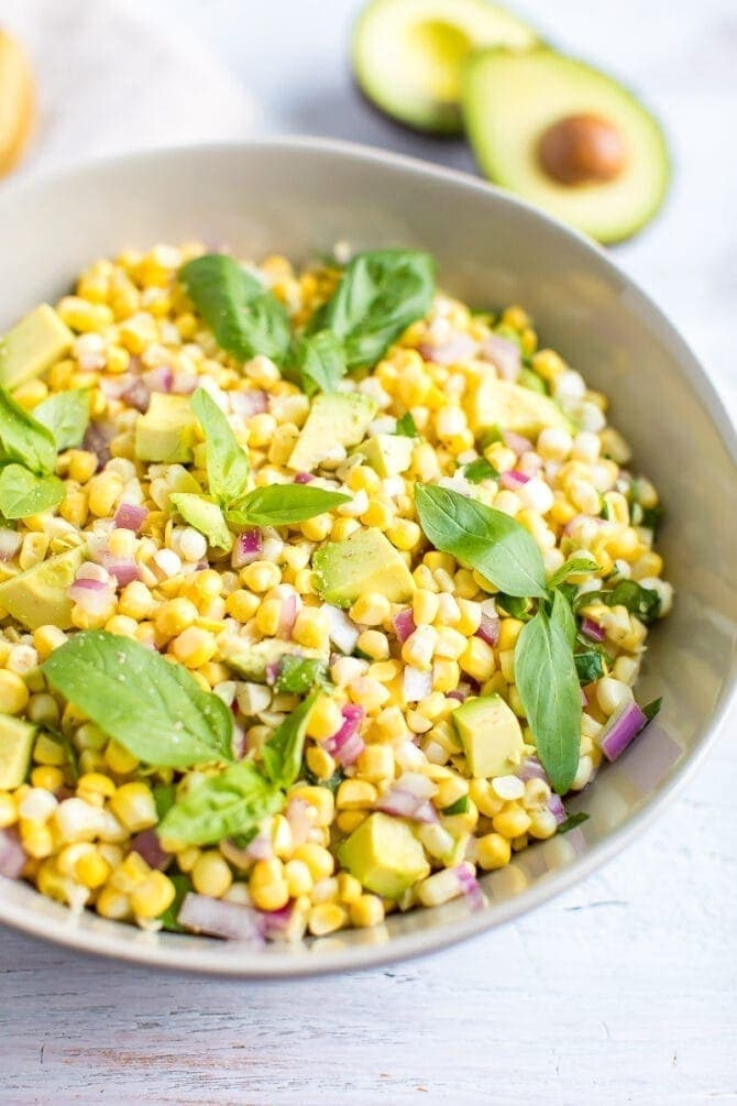 Bowl of avocado and corn salad topped with fresh basil leaves.