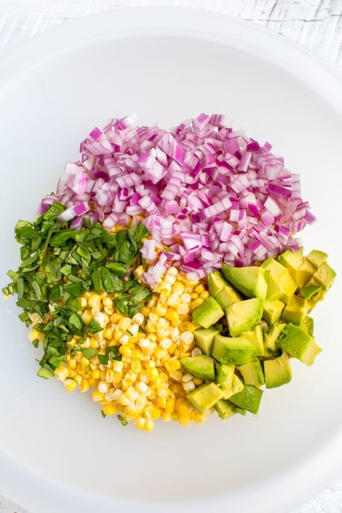 Ingredients for corn and avocado salad in a bowl including basil, corn, red onion and avocado.