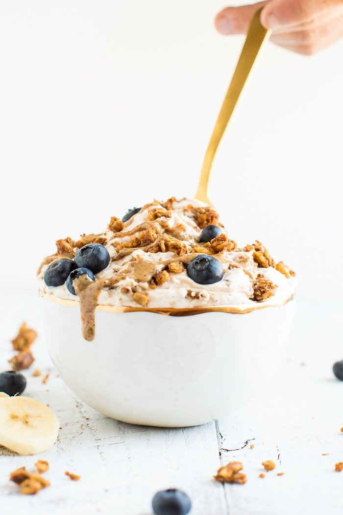A delicious yogurt bowl made with peanut butter, grain-free granola, blueberries and bananas in a gold rimmed bowl with a gold spoon on a white wooden board.
