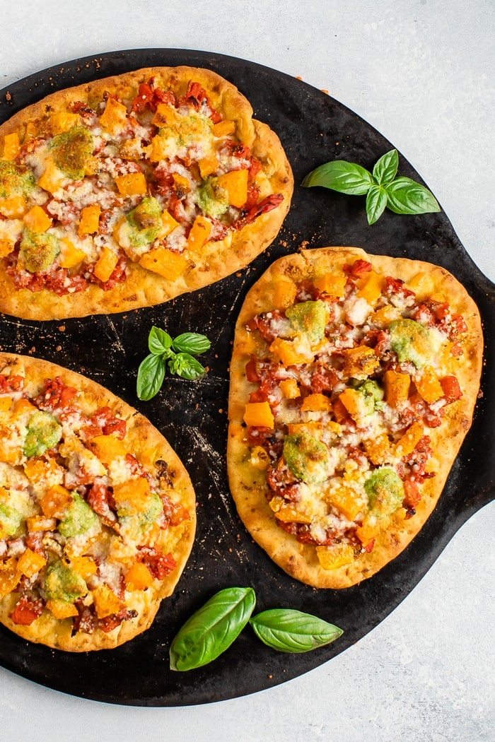 Three naan pizzas with butternut squash and pesto on a round baking stone.