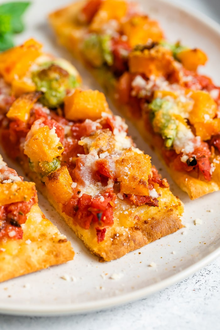 Slices of naan pizza topped with cheese, tomatoes, butternut squash, and pesto.