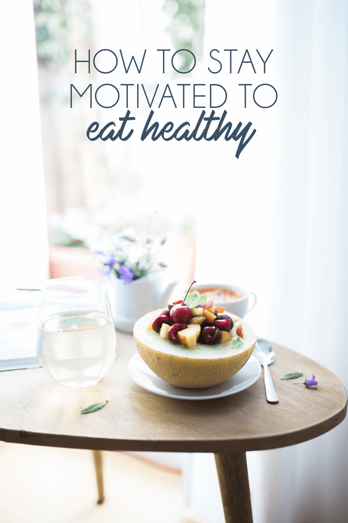Wood table with fruit bow, water, and flowers. 'How to stay motivated to eat healthy' in text overlaying the image.