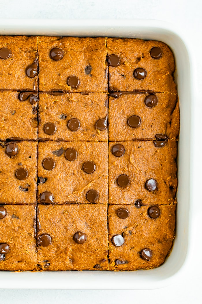 Baking dish with healthy pumpkin bars topped with chocolate chips.