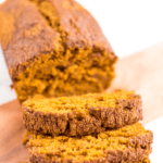 A loaf of healthy low sugar sliced on a cutting board. Text above reads Healthy Low Sugar Pumpkin Bread.