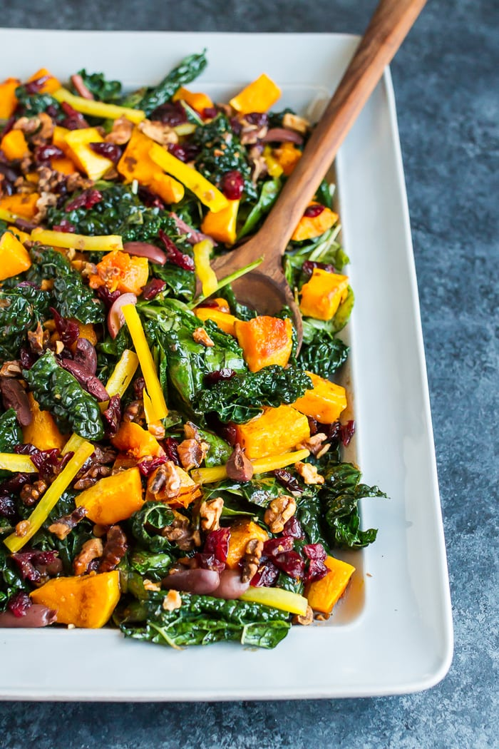 Holiday Kale Salad with Roasted Butternut Squash on a serving plate with a serving spoon.