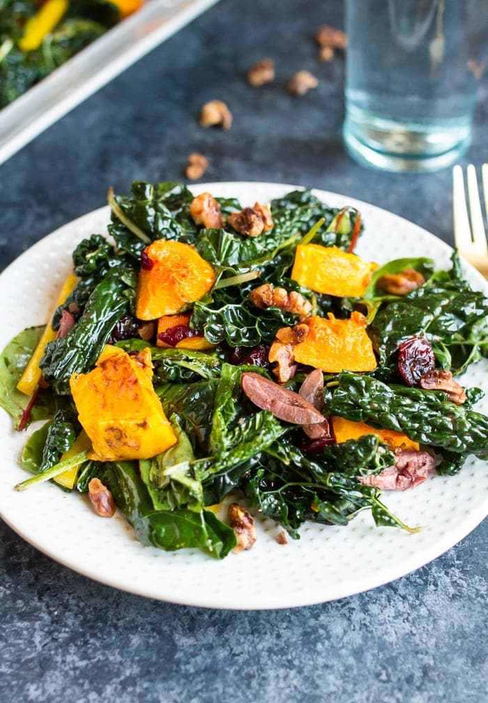 Holiday kale salad with nuts, butternut squash, cranberries, and kalamata olives.