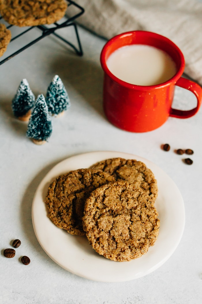 Three almond butter espresso cookies on a plate. Espresso beans, mini Christmas tree decorations and a mug of almond milk in the background.