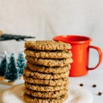 Stack of almond butter espresso cookies, stacked as a tower, on a white plate. A red campfire enamelware mug is in the background along with mini Christmas tree decorations.