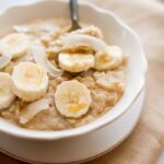 A white bowl of oatmeal covered with slices of banana, pieces of dried coconut, and a honey drizzle. A spoon is sitting in the bowl.
