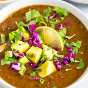 Bowl of black bean soup topped with avocado, cilantro, red cabbage, and lime.