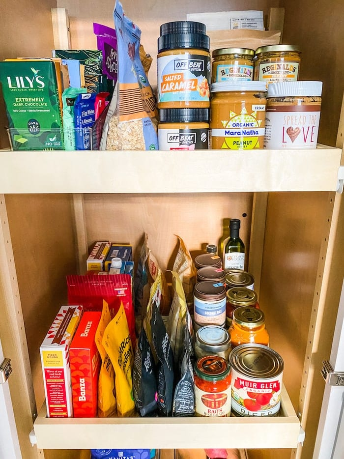 Pantry staples stocked in a pantry like peanut butter, canned goods and bagged foods.