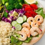 A huge plate with quinoa, greens, shrimp, cucumber, purple cabbage, tomatoes, broccoli, lemon, and asparagus