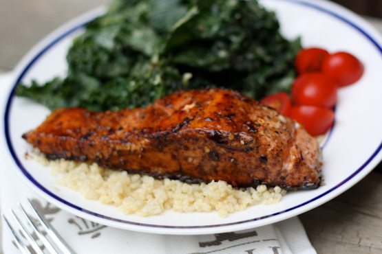White plate with quinoa, balsamic salmon, kale, and tomatoes.