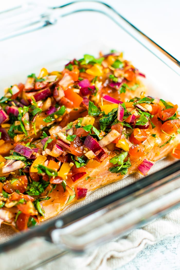 Glass baking dish with baked salmon with herbs and lime.