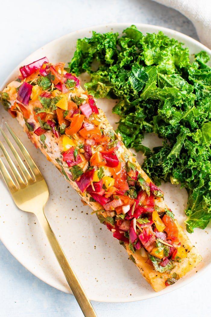 A plate with some greens and baked salmon with herbs and lime served with a golden fork.
