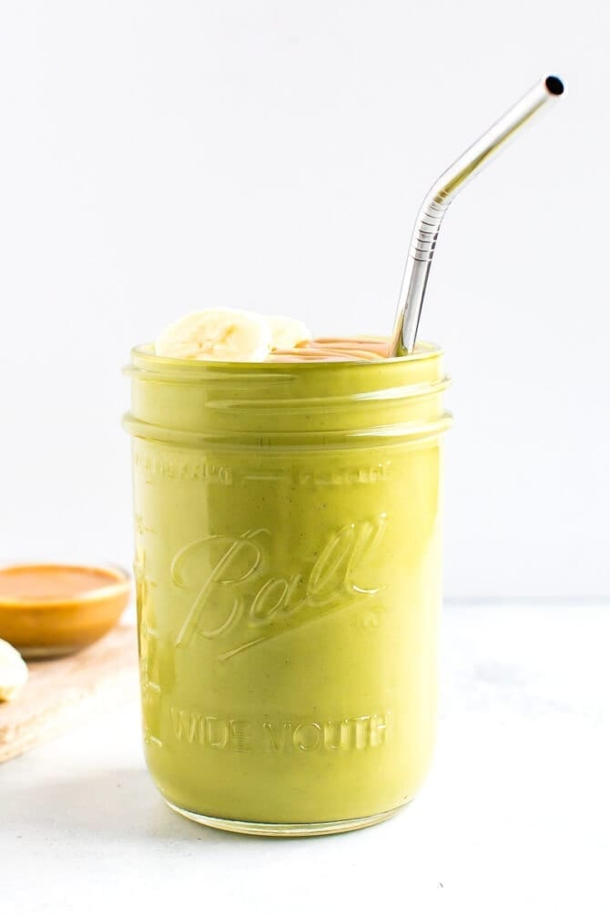 Green smoothie in a jar, topped with banana, peanut butter and a straw. A bowl of peanut butter is behind the jar.