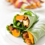 Three collard green wraps filled with, tempeh, creamy hummus, slices of baked sweet potato, green pepper, red onion and cranberries, stacked and sitting on a white plate.