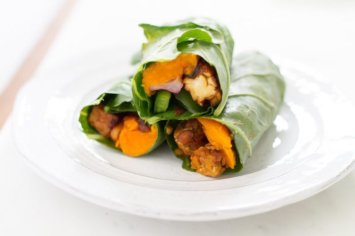 Delicious tempeh collard wraps with creamy hummus, slices of baked sweet potato, green pepper, red onion and cranberries.