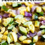 Roasted, chopped summer squash, zucchini, and red onion on a sheet with spices and pepper sprinkled on them.