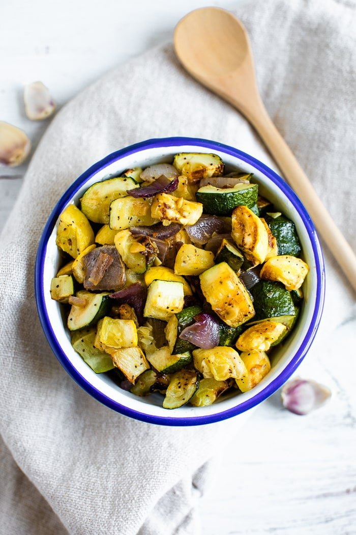Bowl of roasted summer squash, zucchini, and red onion with pepper and seasoning. A wooden spoon is beside the bowl.