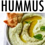 Bowl of lima bean hummus garnished with olive oil, pepper and basil and served with cucumbers, carrots and crackers.