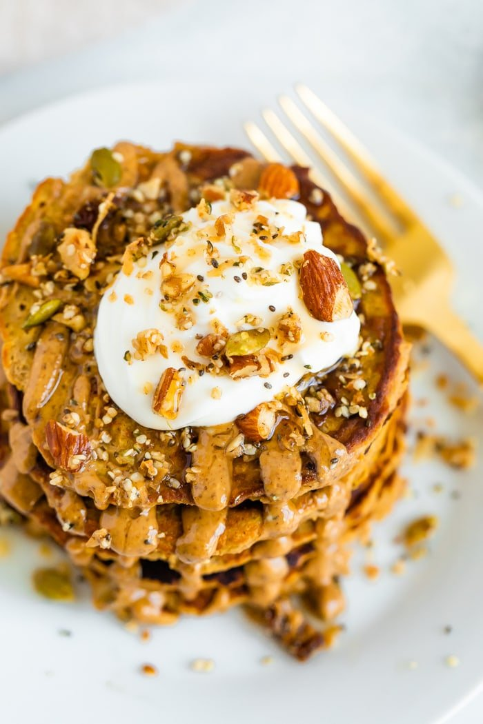 Stack of butternut squash pancakes topped with peanut butter, maple syrup, granola, and yogurt.
