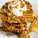 Stack of butternut squash pancakes topped with peanut butter, maple syrup, granola, and yogurt. A bite is cut out of the stack of pancakes and a gold fork is sitting next to the stack.