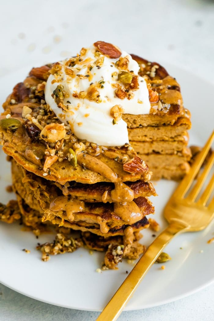 Stack of butternut squash pancakes topped with peanut butter, maple syrup, granola, and yogurt. A slice is taken out of the stack and a fork is resting on the plate.