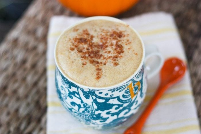 Overhead shot of a Healthy Pumpkin Spice Latte in a blue mug sitting on a kitchen towel.